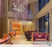 The pastel hued entrance lobby sports a dramatic chandelier