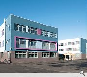 The school is clad in blue and grey brick, render and metal cladding