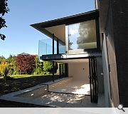 Murphy's trademark crisp white render, horizontal glazing and oversailing roofs are evidenced