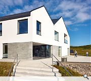 The building is finished in white render, Caithness stone and natural slate
