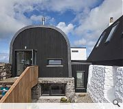 A striking black tarred roof on the guesthouse ties with the surrounding machair landscape
