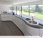 A feature 4m long boomerang shaped worktop dominates the open plan kitchen